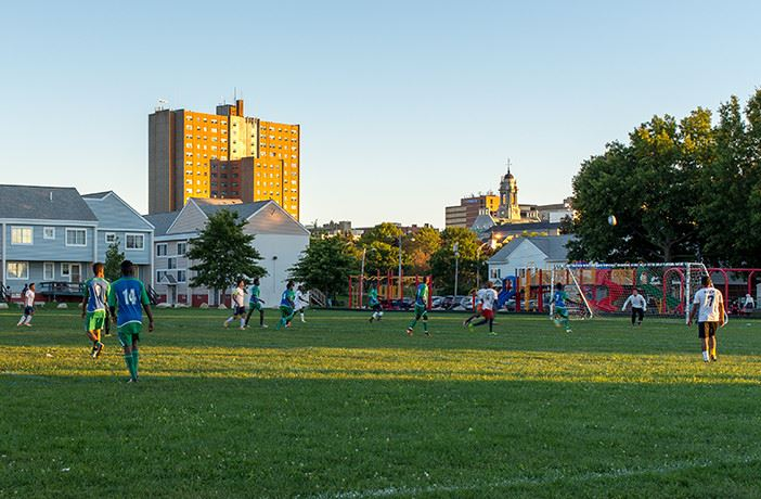 Kids playing soccer with buildings in the background